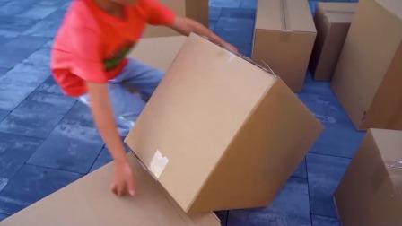 小男孩骑着动力轮汽车玩有趣的纸箱游戏!